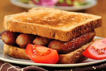 sandwich with some grilled sausages and tomato Stock Photo - 8132346