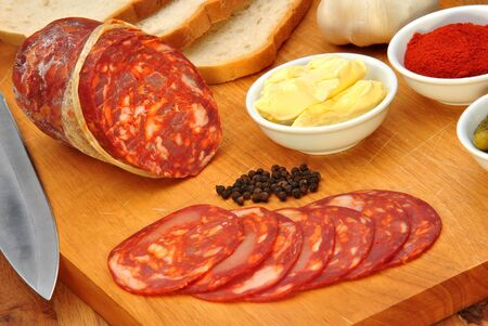 chorizo salami and some slices salami on a timber board photo