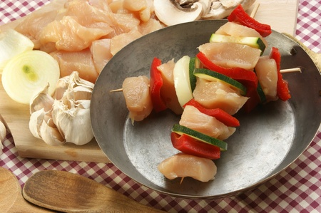 Chicken kebab in a brass pan with organic pepper photo