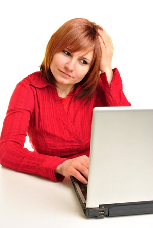 Office assistant in a red blouse working on a laptop Stock Photo - 9463377