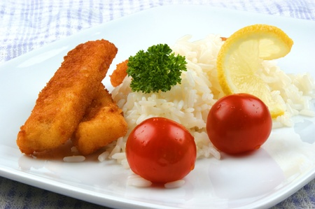 Fish fingers with rice on a plate photo