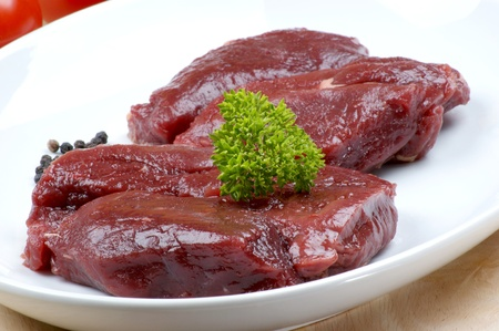 raw ostrich steak with parsley on a plate Stock Photo