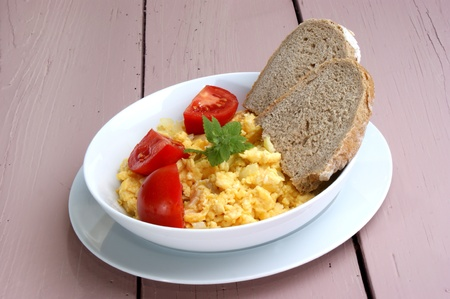 scrambled: Scrambled eggs with tomato and bread in a white bowl Stock Photo