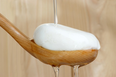 Mozzarella with olive oil on a wooden spoon