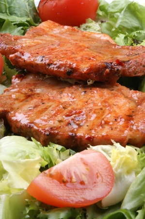 calorie rich food: marinated pork on a bed of lettuce with tomatoes Stock Photo
