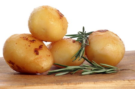 baked potato: roast potatoes with rosemary on a wooden board Stock Photo