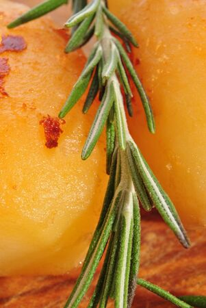 two golden brown roasted potatoes with fresh rosemary Stock Photo - 10415578