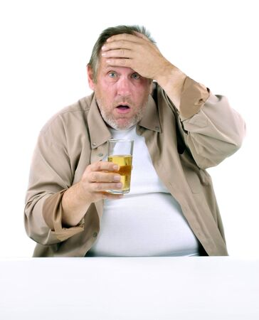 horrified man in his 50s sitting at a table with a drink photo