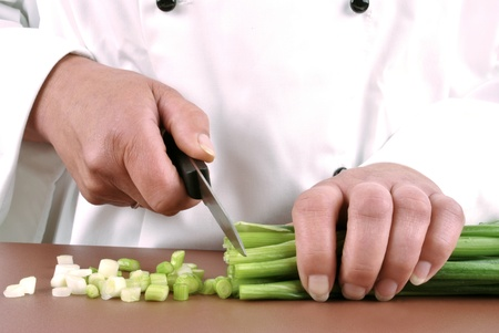 female chef holding a couple of spring onions in her hand photo