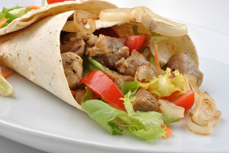taco tortilla: wrap with grilled pork and some vegetable Stock Photo