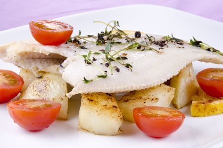 plaice: fresh fried plaice with roasted potatoes and tomatoes Stock Photo
