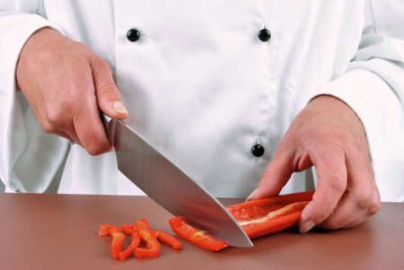 female chef preparing red paprika with a kitchen knife photo