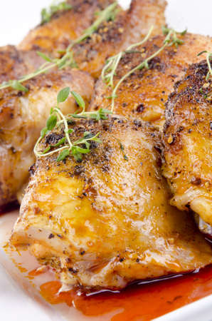 grilled chicken tights with fresh thyme on a white plate photo