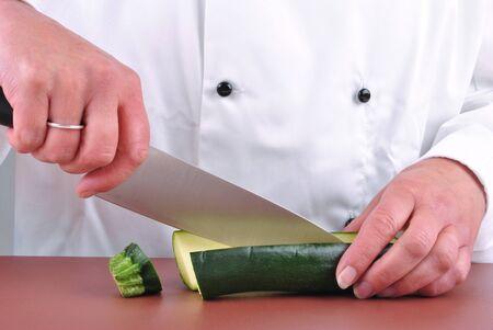 female chef cut one zucchini with a kitchen knife photo