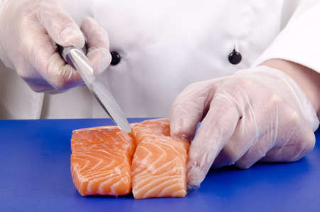 female chef cuts salmon fillets with a kitchen knife photo