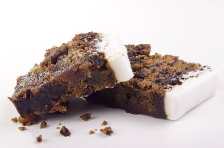 two pieces of iced fruit cake and a white background