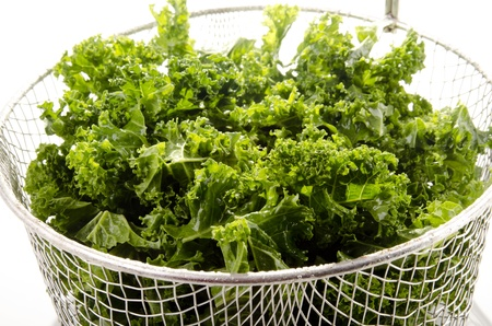 Washed and sliced curly kale in a colander Standard-Bild