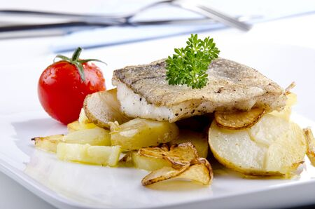 grilled potato: Haddock fillet on a plate with grilled potato and garlic
