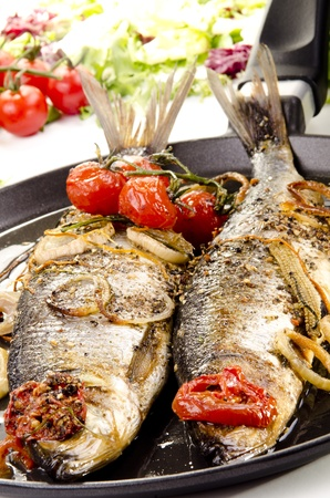 two grilled sea bass in a pan with tomato and onion
