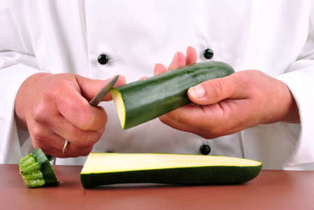 female chef cut one zucchini with a kitchen knife photo