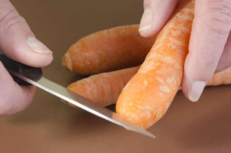 female chef cuts a carrot with a kitchen knife photo