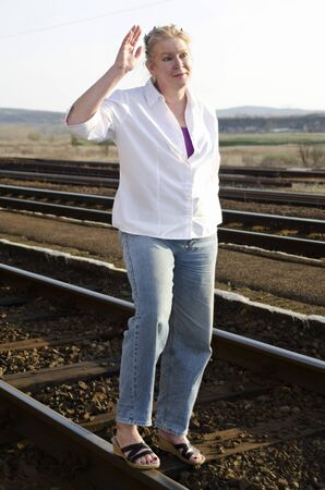 Woman in her 50s is waving on a railway track photo