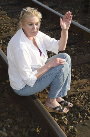 Woman in her 50s sitting and waving on a railway track