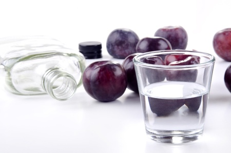 plum brandy in a small glass and fresh plums Standard-Bild