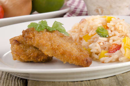 breaded chicken nuggets with rice salad on a plate photo