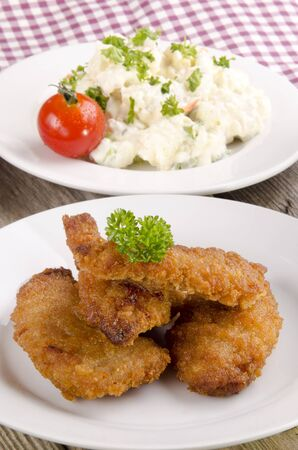 breaded chicken nuggets with potato salad on a plate photo