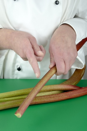 female chef shows with her index finger on organic rhubarb photo