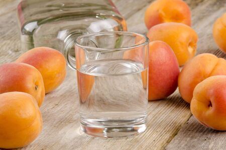 fruit brandy in a glass and fresh apricots in the background