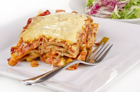 vegetable lasagna with a fork on a plate photo