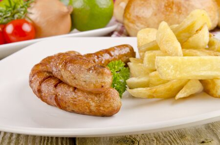 grilled sausages with chips on a plate photo