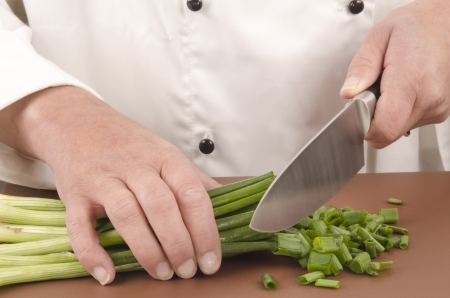 spring onion: female chef cuts fresh spring onion with a large knife