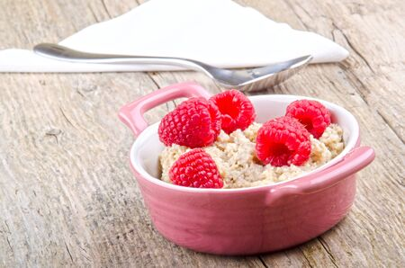 organic raspberry: porridge in a round bowl with fresh organic raspberry