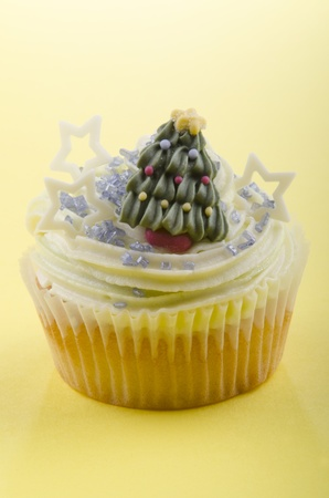 cup cake with mint coloured buttercream,  iced christmas tree and blue shimmer sugar photo