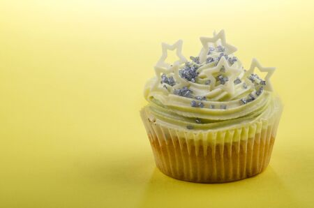 home made cup cake with mint buttercream, white chocolate stars and blue shimmer sugar photo