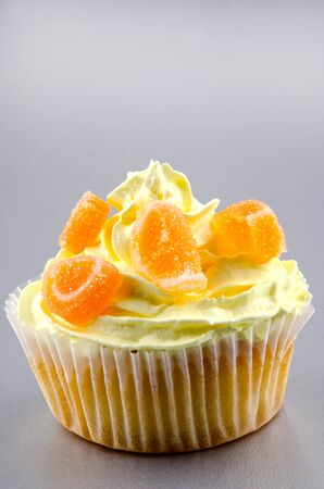 cupcake with lemon buttercream and orange coloured fruit jelly photo
