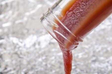 hausgemachte Tomaten-Ketchup fließt aus einer Glasflasche