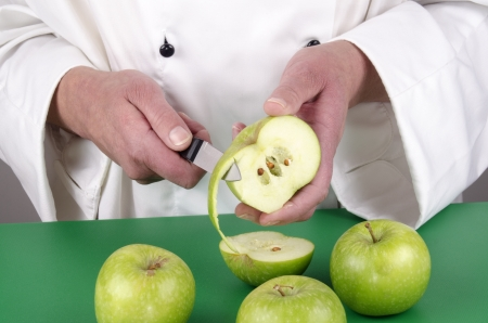 female chef preparing a pear with a kitchen knife photo