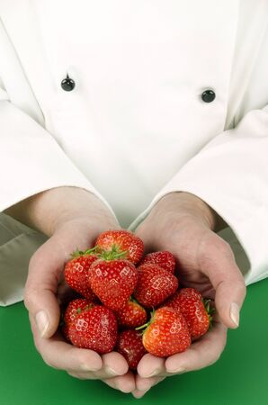 female chef holding some strawberries in her hands photo