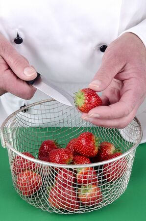 female chef preparing some strawberries with a kitchen knife photo