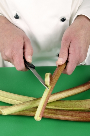female chef preparing some rhubarb with a kitchen knife photo