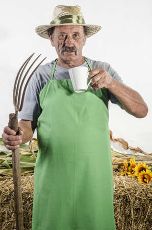 organic farmer with a pitchfork and a cup of coffee during his break photo