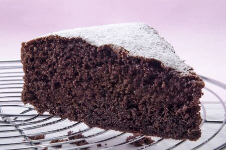 chocolate cake on a baking rack sprinkled with icing sugar Stock Photo