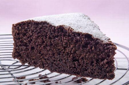 pastel de chocolate: pastel de chocolate sobre una rejilla para hornear espolvoreada con az�car glas Foto de archivo