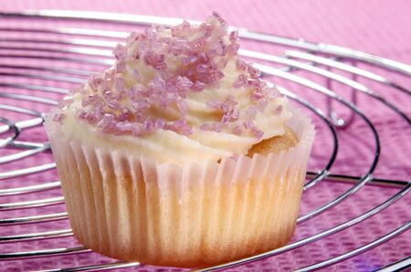 vanilla cupcake: vanilla cupcake with pink sprinkles Stock Photo