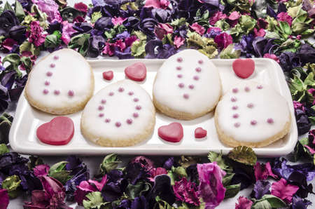 baked cookies with frosting and pink pearls and dry flowers photo