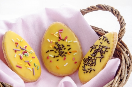three nicely decorated Easter cookies in a basket photo